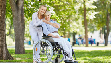 Young female in uniform with senior patient in a wheelchair chilling out in park